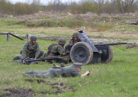 SAINT PETERSBURG, RUSSIA - MAY 05, 2015: German artillery with anti-tank gun into position. Reconstruction of the episode of the great Patriotic war Editorial