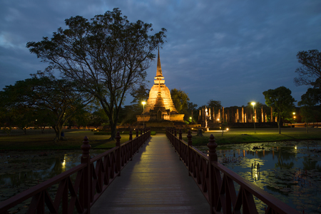 The wooden bridge conducting to ruins of the ancient Buddhist temple of Wat Sa Si in evening twilight. Historical park of the Sukhothai, Thailand Stock Photo