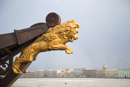 SAINT PETERSBURG, RUSSIA - MARCH 20, 2017: Golden statue of a lion on the nose of the old ship on the background of the Palace embankment cloudy March afternoon