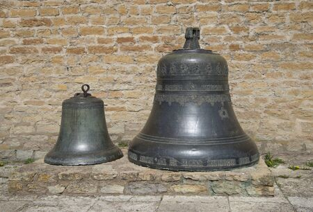 herman: Two vintage bell against the wall of the castle of Herman. Narva, Estonia Editorial