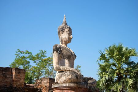 A view of the ancient sculpture of a sitting Buddha on the ruins of the Buddhist temple of Wat Mae Chon on a sunny afternoon. Sukhothai, Thailand Stock Photo