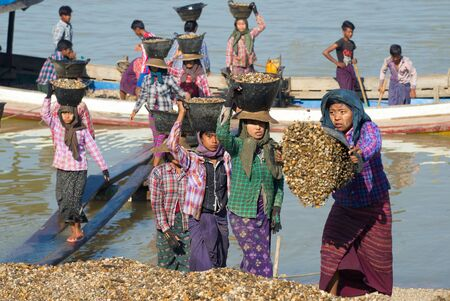 BAGAN, MYANMAR - DECEMBER 23, 2016: Burmese girls unload the barge with the river gravel