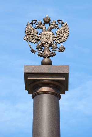 stele: KRONSTADT, RUSSIA - JULY 18, 2015: Two-headed Russian eagle on top of a column against a blue sky. Fragment of the monument of military glory