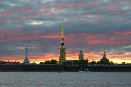 The Peter and Paul Fortress under the gloomy sunset sky in the May evening. St. Petersburg, Russia
