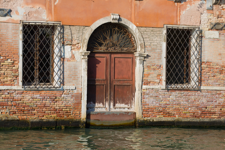 Fragment of the façade of the flooded old house. Venice, Italy