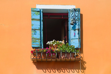 Old window with flowers and blue shutters in a wall of the orange house. Italy