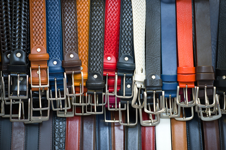 FLORENCE, ITALY - SEPTEMBER 19, 2017: Hanging multi-colored leather belts close-up. City Market of Florence