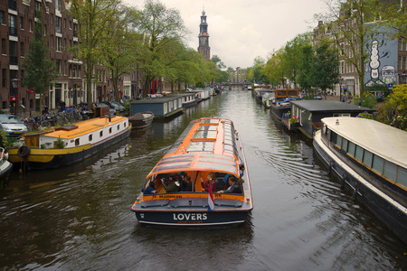 AMSTERDAM, NETHERLANDS - SEPTEMBER 30, 2017: Pleasure boat on the Prinsengracht canal on a cloudy September day