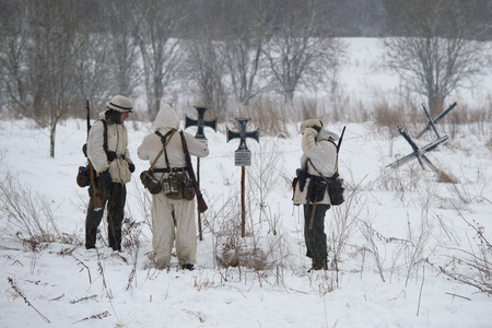 KRASNOE SELO, RUSSIA - JANUARY 15, 2017: The German infantrymen of the period of World War II at the field cemetery. Fragment of military and historical reconstruction of fights for lifting the siege of Leningrad