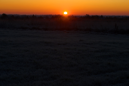 October sunrise on a frozen field. Pskov region, Russia