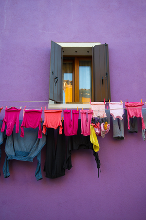 Drying linen in the background of a window on a lilac wall. Burano Island, Venice