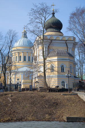 ST. PETERSBURG, RUSSIA - MARCH 30, 2016: St. Nicholas Church in the background of the Trinity Cathedral on a sunny April day. Nikolsky Cemetery of the Alexander Nevsky Lavra