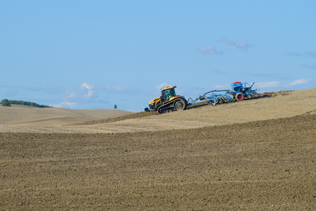 TUSCANY, ITALY - SEPTEMBER 21, 2017: Tracked tractor Challenger MT765D with pneumatic seed drill Lemken Solitair 9 works in the field on a sunny September day