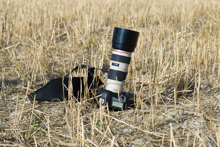 SLR camera with telephoto lens on a beveled field