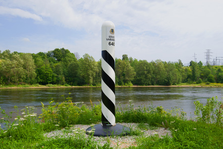 The Estonian boundary post against the background of the river Narva in the cloudy August afternoon. Border of Estonia and Russia Redactioneel