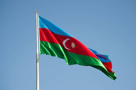 The national flag of Azerbaijan is flying in the blue sky