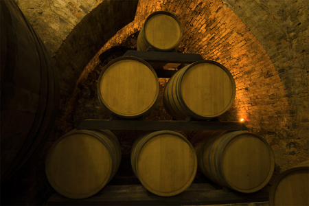 Barrels of young wine in the old wine cellar of Montepulciano. Tuscany, Italy
