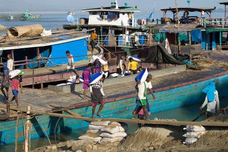 MANDALAY, MYANMAR - DECEMBER 21, 2016: Unloading a barge in the river port