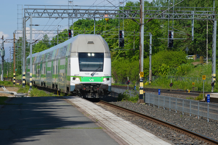 HAMEENLINNA, FINLAND-JUNE 10, 2017: Modern double-Decker train coming to the platform of the railway station on a sunny summer day