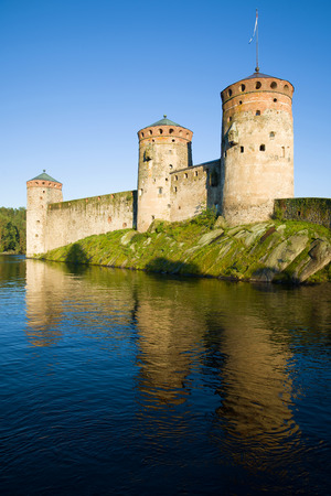 Towers of the Olavinlinna fortress in the rays of the setting sun in the August evening. Savonlinna, Finland Editorial
