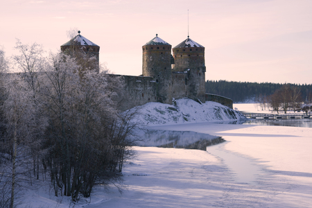 Winter morning in purple tones near the fortress of Olavinlinna. Savonlinna, Finland