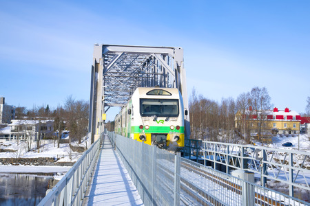 SAVONLINNA, FINLAND - MARCH 03, 2018: The passenger train passes by the railway bridge on a winter day Editorial