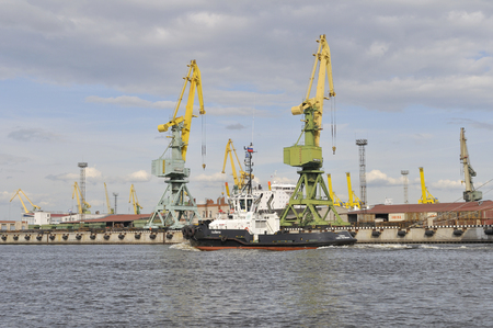 SAINT PETERSBURG, RUSSIA - JUNE 19, 2010: Two cranes and a tug at the port Editorial