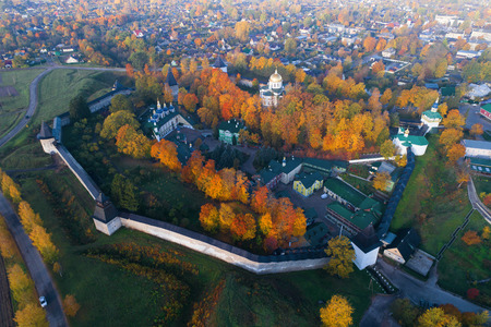 The Holy Dormition Pskovo-Pechersky Monastery in the city panorama on the golden autumn (aerial survey). Pechory, Russia