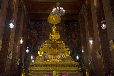 BANGKOK, THAILAND - DECEMBER 28, 2018: Sculpture of a seated Buddha on a throne. Interior of Phra Ubosot of Buddhist Temple of Wat Pho
