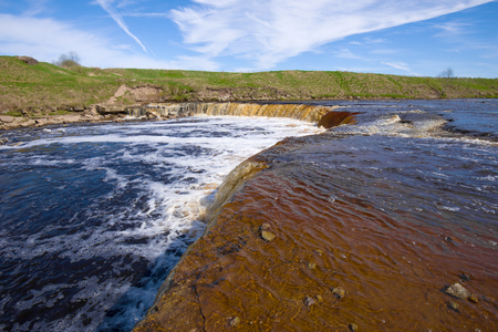 On the edge of Tosno waterfall Sunny may day. The Tosna river. Leningrad region, Russia Stockfoto