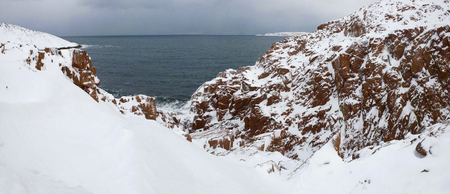 February day on the rocky shore of the Barents Sea. The surroundings of the village Teriberka. Murmansk region, Russia 免版税图像