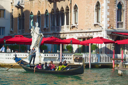 VENICE, ITALY - SEPTEMBER 26, 2017: Sad gondolier with cheerful tourists on the Grand Canal on a sunny afternoon