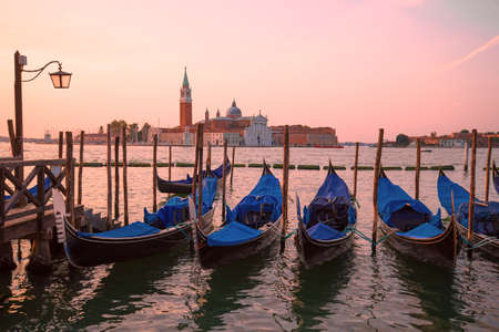 Moored gondolas on the background of the Cathedral of San Giorgio Maggiore on sunrise. Venice, Italy