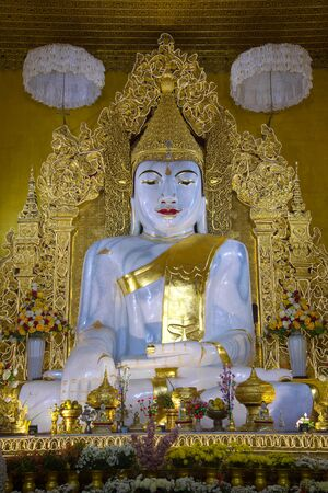 A large sculpture of a sitting Buddha in a Buddhist temple Kyauktawgyi Pagoda close up. Mandalay, Myanmar Redactioneel