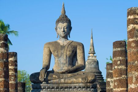 Ancient sculpture of a sitting Buddha close up on a sunny day. The ruins of the Buddhist temple of Wat Chana Songkhram. Sukhothai, Thailand Editorial