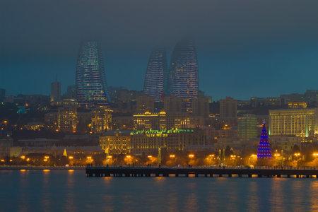 BAKU, AZERBAIJAN - JANUARY 04, 2018: Flame towers in the cityscape on a foggy January evening