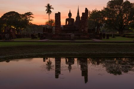 Sculpture of a sitting Buddha on the ruins of a Buddhist temple Wat Chana Songkram on sunset background. Sukhothai Historical Park, Thailand