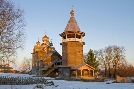 The old wooden church of Dmitri the Theunite Myrrh-streaming in close-ups in the rays of the setting sun on April evening. Village Shcheleyki, Leningrad Region, Russia