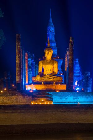 The ancient sculpture of the sitting Buddha on ruins of the Buddhist temple Wat Makhatkhat in blue night illumination. Sukhothai, Thailand