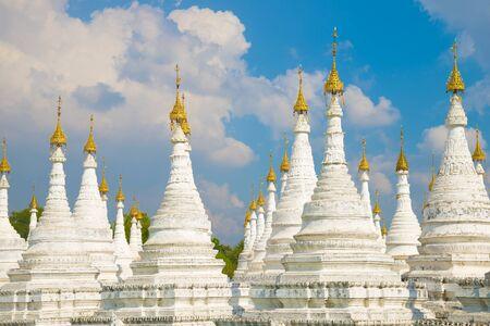 White stupas of the Sanda Muni pagoda against a cloudy blue sky. Mandalay, Myanmar Stockfoto
