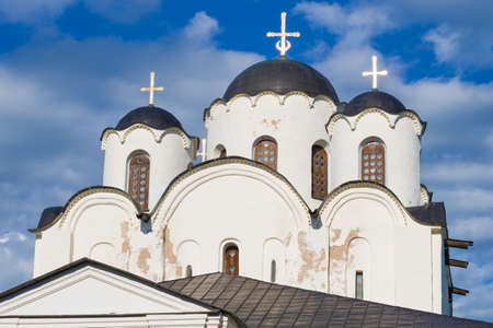 The top of the Nikolo-Dvorishchenskiy Cathedral (1113) close-up on a background of cloudy sky. Veliky Novgorod, Russia