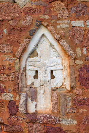 Ancient embedded cross with crucifixion close-up. Fragment of the design of the Church of the Transfiguration of the Savior on Kovalev (XIV-XV centuries). Surroundings of Veliky Novgorod, Russia Stok Fotoğraf