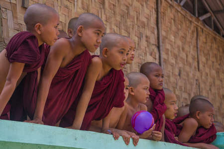 YANGON, MYANMAR - DECEMBER 18, 2016: Boys novices of Buddhist monastery look out of the fence