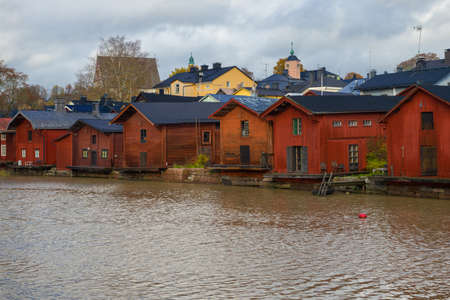 Old wooden houses on the banks of the Porvoonjoki river on a cloudy October day. Porvoo city symbol, Finland
