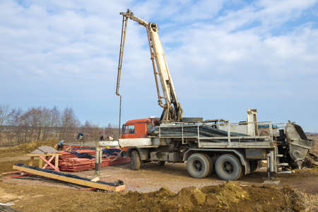 LENINGRAD REGION, RUSSIA - MARCH 28, 2021: A concrete pump based on a Kamaz truck on the construction site of a country house on a sunny spring day