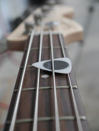 guitar pick: black& white guitar pick on the fingerboard