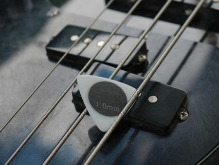 guitar pick: black& white guitar pick on the pickup guitar bass Stock Photo