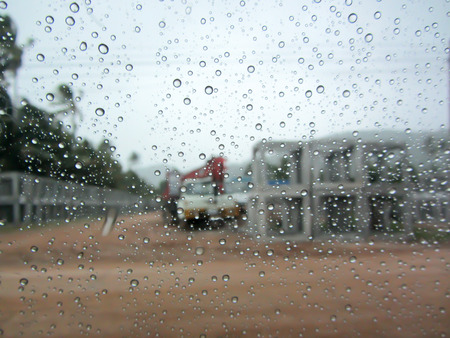auto glass: Rain drop on auto glass with Construction background in rainy day