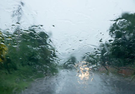 auto glass: rain drop on front auto glass in rainy day view in side car