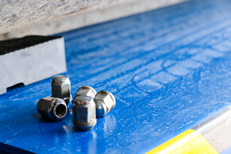 four lug nuts on the ground when replacing wheelsWheel equipment
